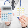 Doctor holdling calculator and pills in his hands - heath care concept — Stock Photo #53402425