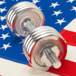 Metal dumbbell over US flag as symbol of healthy life style — Zdjęcie stockowe