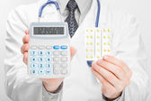 Doctor holdling calculator and pills in his hands - heath care concept — Stock Photo