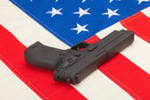 Handgun laying over USA flag - studio shoot — Stock Photo
