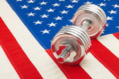 Metal dumbbell over US flag as symbol of healthy life style - studio shot — Stock Photo