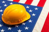 Construction helmet laying over USA flag - closeup shoot — Foto Stock