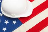White color construction helmet laying over US flag — Stock Photo