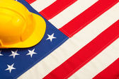 Construction helmet laying over US flag — Foto Stock
