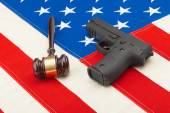 Wooden judge gavel and gun over USA flag - studio shot — Stock Photo