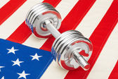 Metal dumbbells over US flag as symbol of healthy nation - studio shot — Stock Photo