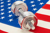Metal dumbbell over US flag as symbol of healthy life style — Stock Photo