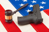 Wooden judge gavel and gun over US flag - studio shot — Stock Photo