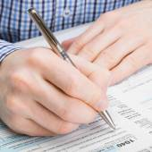 Male filling out 1040 United States of America Tax Form - studio shot - 1 to 1 ratio — Stock Photo