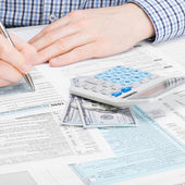Male filling out 1040 USA Tax Form - studio shot - 1 to 1 ratio — Stock Photo