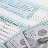 USA Tax Form 1040 with 100 US dollar bills - 1 to 1 ratio — Foto de Stock
