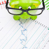Green piggy bank over stock market chart - view from top - 1 to 1 ratio — Stock Photo