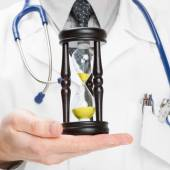 Doctor holdling in his hand a hourglass - heath care concept - 1 to 1 ratio — Foto de Stock