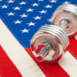Metal dumbbell over US flag as symbol of healthy life style - 1 to 1 ratio — Zdjęcie stockowe