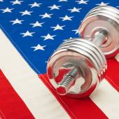 Metal dumbbell over US flag as symbol of healthy life style - 1 to 1 ratio — Stock Photo