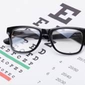 Table for eyesight test with glasses over it - 1 to 1 ratio — Stock Photo