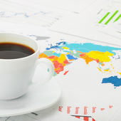 Cup of coffee over world map and financial documents - 1 to 1 ratio — Stock Photo