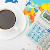 Coffee cup over world map and financial documents - view from top - 1 to 1 ratio — Stock Photo