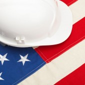 White color construction helmet laying over US flag - 1 to 1 ratio — Stock Photo