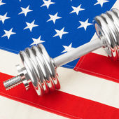 Metal dumbbells over USA flag as symbol of healthy nation - 1 to 1 ratio — Foto de Stock
