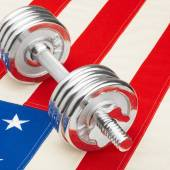 Metal dumbbells over US flag as symbol of healthy nation - 1 to 1 ratio — Foto de Stock