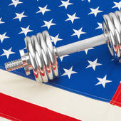 Metal dumbbell over US flag as symbol of healthy nation - 1 to 1 ratio — Foto de Stock