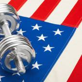 Metal dumbbell over US flag as symbol of healthy nation - 1 to 1 ratio — Stock Photo