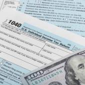 US Tax Form 1040 with 100 dollars banknote above it - 1 to 1 ratio — Stock Photo