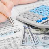Male filling out 1040 US Tax Form with calculator and money on table - 1 to 1 ratio — Stockfoto