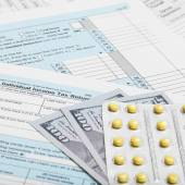 US Tax Form 1040 with 100 dollars and pills - 1 to 1 ratio — Stock Photo