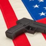 Studio shot of handgun over USA flag - 1 to 1 ratio — Stock Photo #53911119