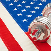 Metal dumbbell over big US flag as healthy life style concept - 1 to 1 ratio — Stock Photo