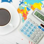 Coffee cup and calculator over world map and financial charts - 1 to 1 ratio — Stockfoto
