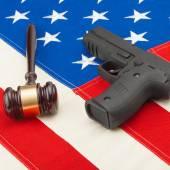 Wooden judge gavel and gun over big USA flag - 1 to 1 ratio — Stock Photo