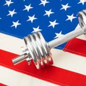 Metal dumbbells over big US flag as symbol of healthy nation - 1 to 1 ratio — Stock Photo