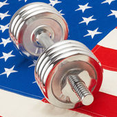 Metal dumbbell over big US flag - symbol of healthy life style - 1 to 1 ratio — Stock Photo