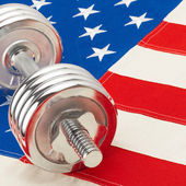 Metal dumbbell over big US flag - healthy life style concept - 1 to 1 ratio — Stock Photo