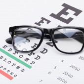 Table for eyesight test with neat glasses over it - 1 to 1 ratio — Stock Photo
