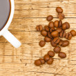 Wooden table with white ceramic coffee cup and roasted coffee beans on it - 1 to 1 ratio — Stock Photo #55147537