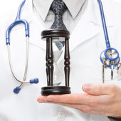 Doctor with hourglass in hand - 1 to 1 ratio — Stock Photo