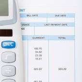 Calculator next to bill - studio shot - 1 to 1 ratio — Stock Photo