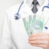Doctor holding money in his hand - 1 to 1 ratio — Stock Photo