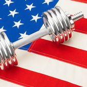 USA flag and metal dumbbells as symbol of healthy nation - studio shot - 1 to 1 ratio — Stock Photo