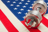 Dumbbell over USA flag as symbol of healthy nation — 图库照片