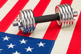 Dumbbell over US flag as symbol of healthy nation — 图库照片