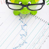 Green piggy bank over stock chart - view from top — Stock Photo