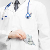 Doctor putting money into his pocket — Stock Photo