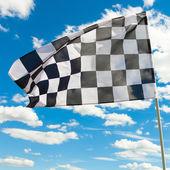 Bandera a cuadros en el cielo azul con nubes — Foto de Stock