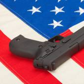 Handgun laying over USA flag — Stock Photo
