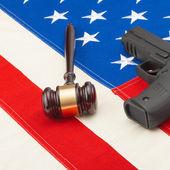 Neat judge gavel and gun over US flag - studio shot — Stock Photo